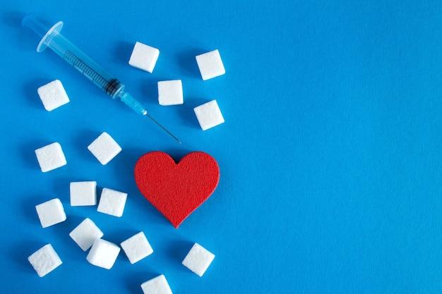 Coração vermelho com cubos de açúcar e seringa Foto Premium