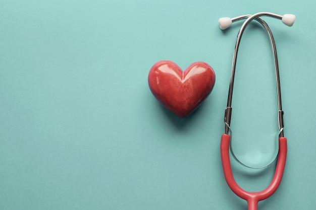 Coração vermelho com estetoscópio, saúde do coração, conceito de seguro de saúde, dia mundial do coração, dia mundial da saúde Foto Premium