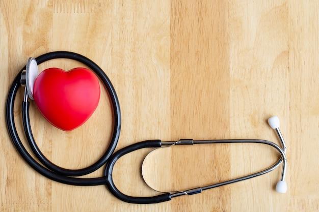 Coração vermelho e estetoscópio na mesa de madeira Foto Premium