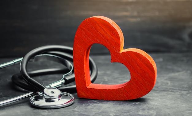 Coração vermelho e estetoscópio. o conceito de medicina Foto Premium