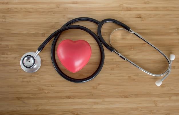 Coração vermelho e um estetoscópio na mesa de madeira, campanha do dia mundial da saúde Foto Premium