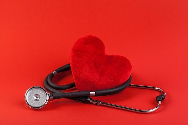 Coração vermelho e um estetoscópio Foto Premium