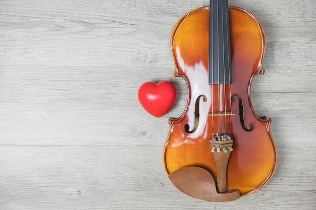Coração vermelho e violão clássico de madeira na mesa cinza Foto gratuita