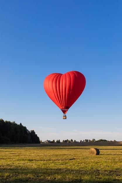 Coração vermelho em forma de balão de ar sobrevoando os campos com montes de feno Foto Premium