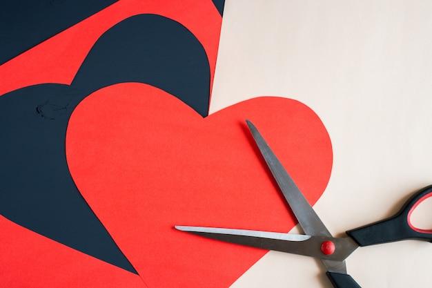 Coração vermelho esculpida em tesoura e folha de papel Foto Premium