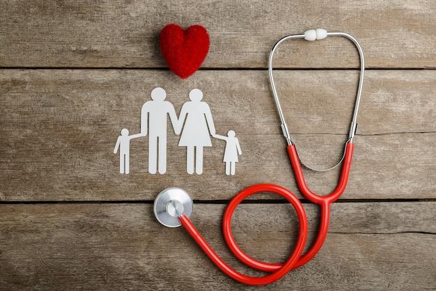 Coração vermelho, estetoscópio e papel família cadeia na mesa de madeira Foto Premium