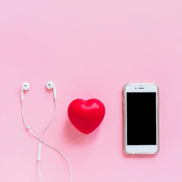 Coração vermelho; fone de ouvido e smartphone em fundo rosa Foto gratuita