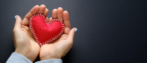 Coração vermelho ou valentine nas mãos de uma menina, sobre um fundo preto. o conceito de comemorar o dia dos namorados. símbolo do amor. bandeira. Foto Premium