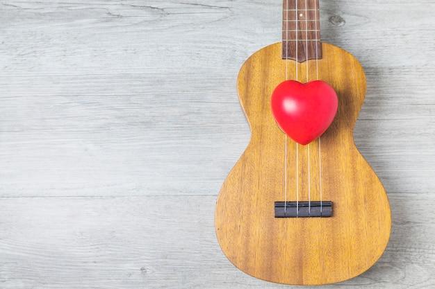 Coração vermelho sobre a guitarra de madeira sobre a prancha de madeira Foto gratuita