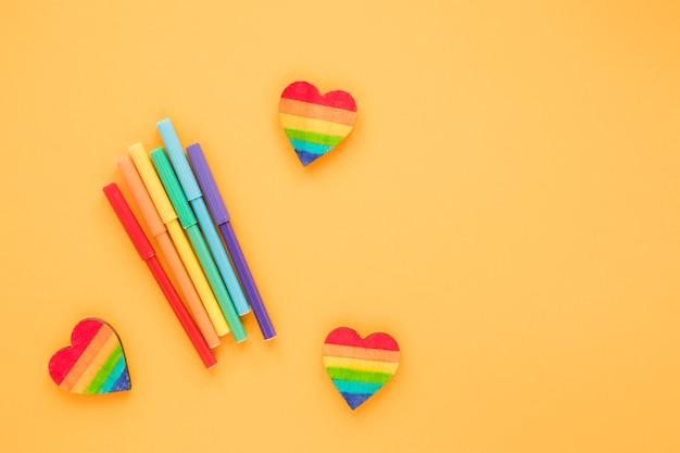 Corações de arco-íris com canetas de feltro na mesa Foto gratuita