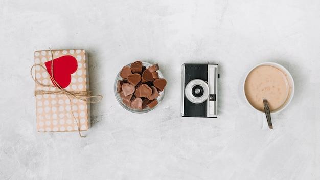 Corações de chocolate, caixa de presente, câmera e copo de bebida Foto gratuita