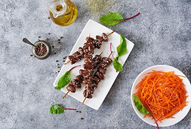 Corações de frango em molho picante e salada de cenoura. comida saudável. vista do topo Foto Premium