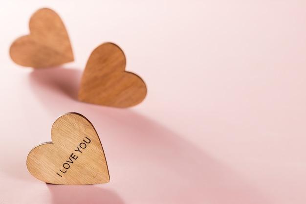 Corações de madeira no fundo rosa Foto Premium