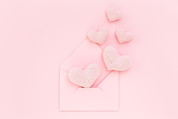 Corações de malha rosa em envelope em fundo rosa. dia dos namorados. amo confessar. postura plana. Foto Premium