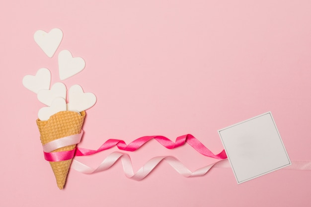 Corações de papel em bastões de waffle perto de cartão postal Foto gratuita