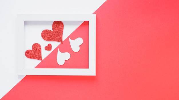 Corações de papel entre moldura Foto gratuita