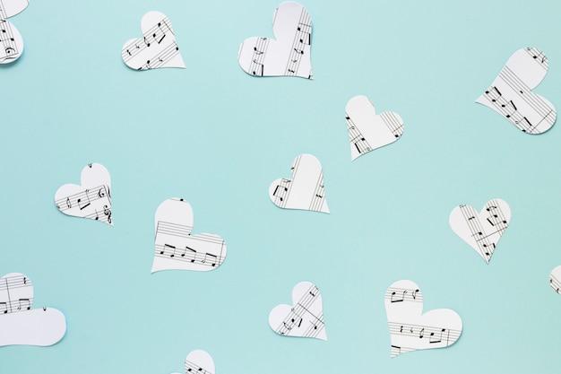 Corações de papel liso leigos sobre fundo azul Foto gratuita