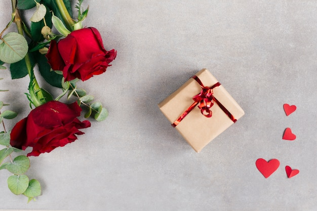 Corações de papel perto de caixa presente no envoltório e flores Foto gratuita