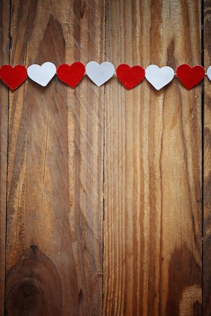 Corações de papel vermelho e branco no varal de madeira backgrou Foto Premium