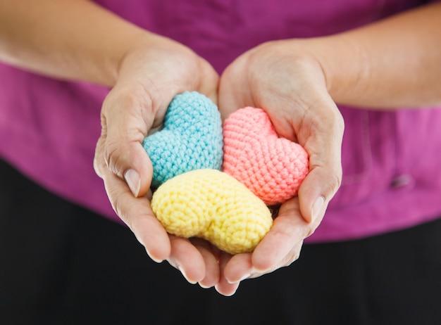 Corações de tricô multicolor coloridas realizada por ambas as mãos da fêmea, representando a mão amiga Foto Premium