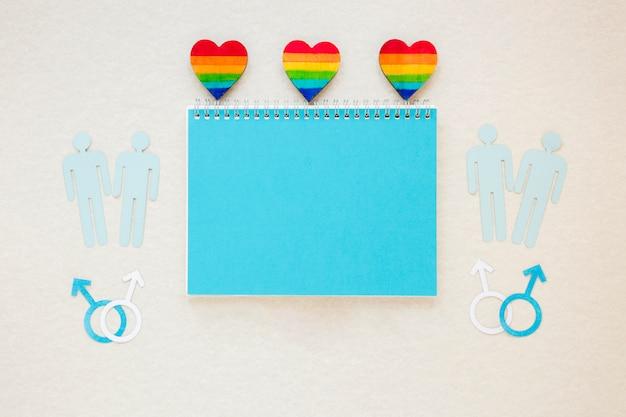 Corações do arco-íris com ícones de casais gays e o bloco de notas Foto gratuita
