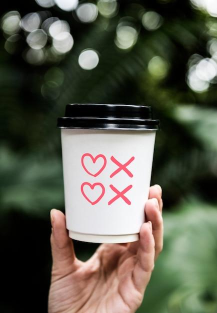 Corações e beijos símbolos em uma xícara de café de papel Foto Premium