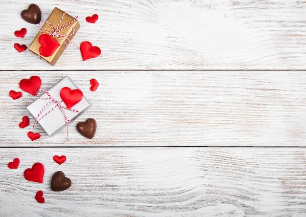 Corações e caixas de presente na superfície de madeira Foto Premium