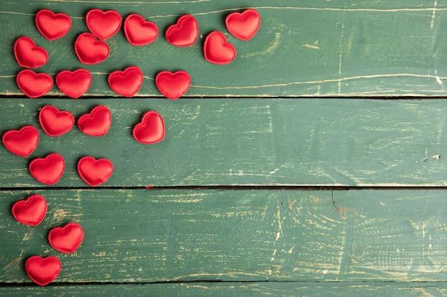Corações no papel de parede verde Foto gratuita