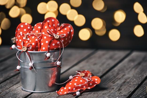 Corações vermelhos em balde de zinco em fundo de madeira em estilo vintage e retrô. conceito de dia dos namorados. Foto Premium