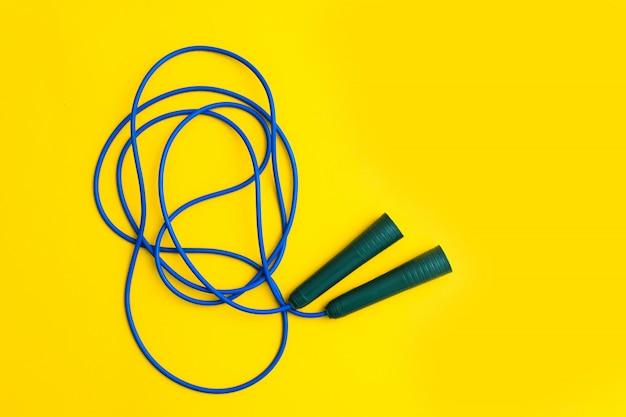 Corda de pular fitness azul para pular com alças de plástico em fundo amarelo Foto Premium