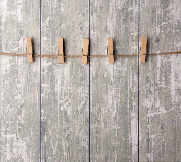 Corda marrom e prendedores de roupa de madeira, plano de fundo para o designer Foto Premium