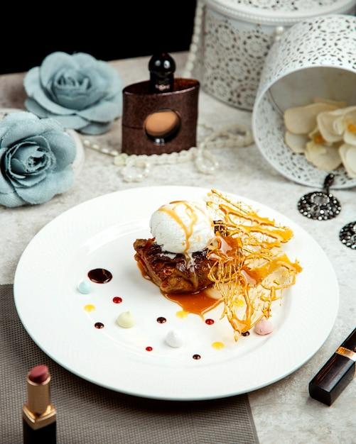Cordeiro frito coberto com sorvete de baunilha, colocado ao lado de batom e perfume Foto gratuita