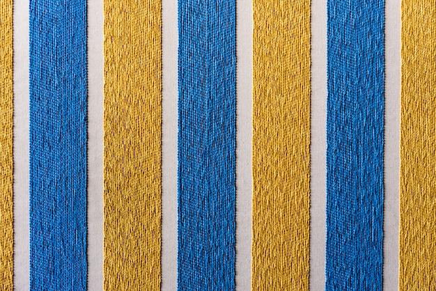 Cores azuis e amarelas listradas com textura áspera da tela, fundo colorido. Foto Premium