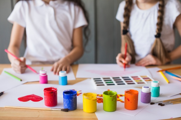 Cores de tinta colorida na frente de uma garota de pintura sobre o livro branco sobre a mesa Foto gratuita