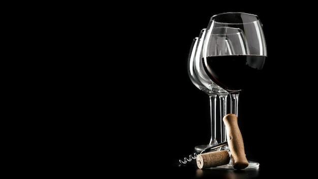 Corkscrew e cortiça perto de copos de vinho Foto gratuita