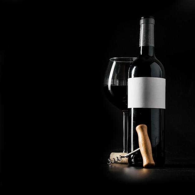 Corkscrew perto de garrafa e copo de vinho Foto Premium