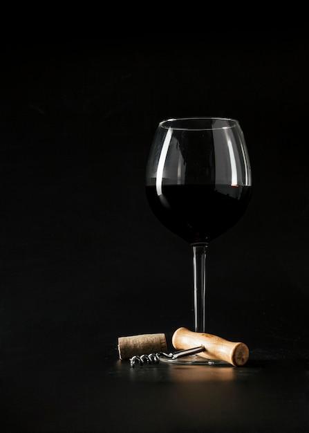 Corkscrew perto de um copo de vinho Foto gratuita