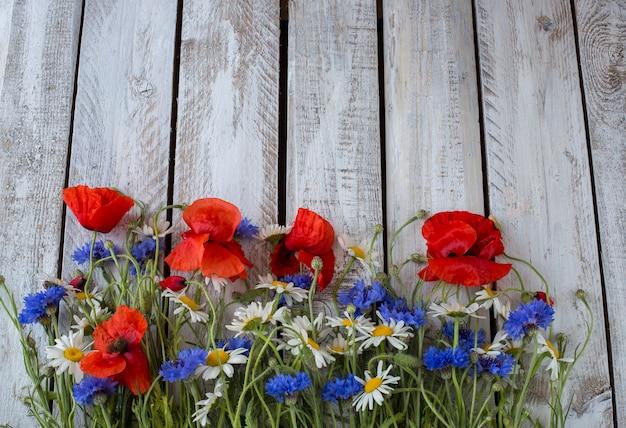 Cornflowers, camomila, papoulas sobre uma mesa de madeira branca Foto Premium