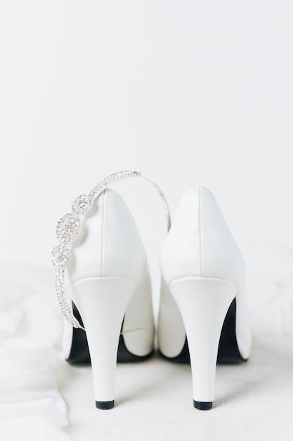 Coroa de diamante sobre o par de saltos altos de casamento branco contra o pano de fundo branco Foto gratuita