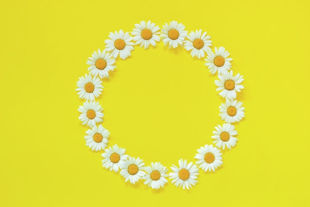 Coroa de flores redonda floral de camomila flores sobre fundo amarelo Foto Premium