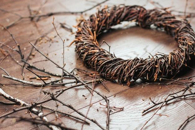 Coroa de vime de ramos de bétula, sobre um fundo de madeira. tecendo uma coroa de ramos. Foto Premium
