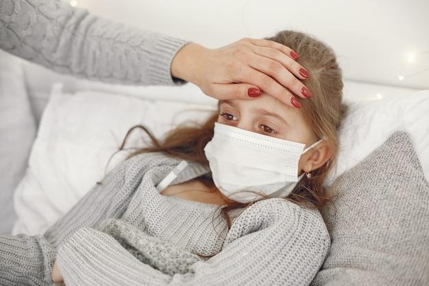 Coronavírus em criança. mãe com filha. criança deitada em uma cama. mulher com uma máscara médica. Foto gratuita