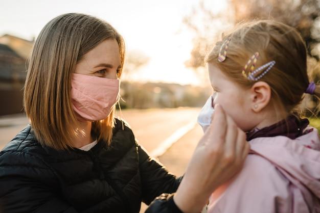 Coronavírus o conceito final. não há mais covid-19. menina, mãe usar máscaras andar na rua. mãe remove máscara criança feliz. família com criança ao ar livre. comemorando o sucesso. a pandemia acabou, terminou. Foto Premium