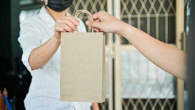 Corpo a corpo peça produtos e alimentos entregues em casa para impedir a transmissão do coronavírus ou da covid-19. Foto Premium