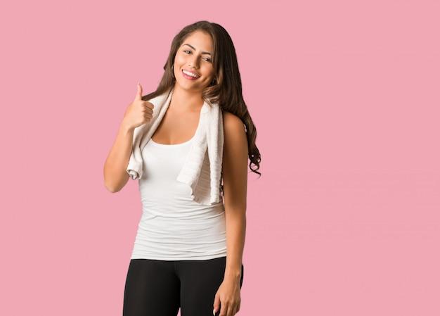 Corpo cheio de fitness jovem mulher curvilínea sorrindo e levantando o polegar para cima Foto Premium