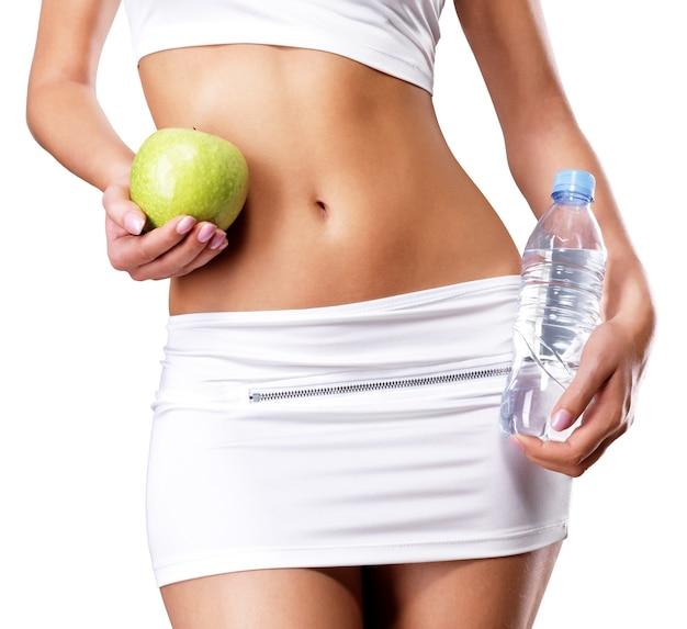 Corpo feminino saudável com maçã e garrafa de água. aptidão saudável e comer o conceito de estilo de vida. Foto gratuita