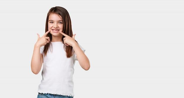 Corpo inteiro menina sorri, apontando a boca, conceito de dentes perfeitos, dentes brancos, tem uma atitude alegre e jovial Foto Premium