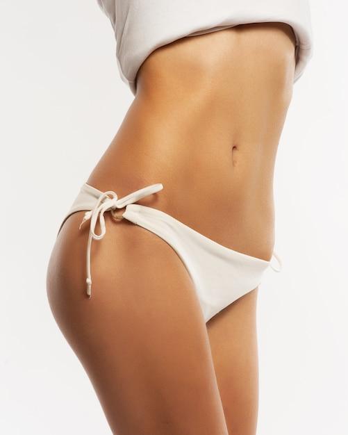 Corpo magro da mulher bronzeada. isolado sobre o fundo cinza. Foto Premium