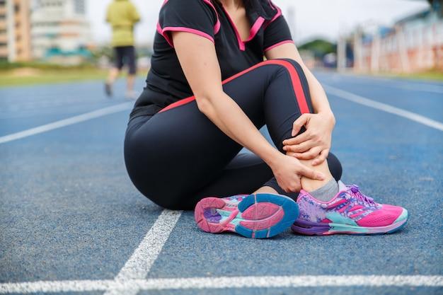 Corredor atleta atleta lesão no tornozelo e dor. mulher que sofre de tornozelo doloroso enquanto corre na pista de corrida azul emborrachada. Foto Premium