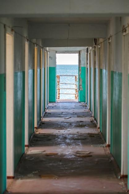 Corredor com portas em prédio abandonado durante o dia e vista mar. Foto Premium